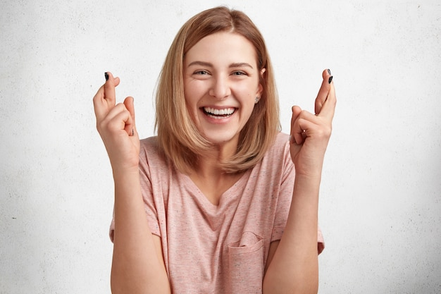 Ainda bem que a bela jovem aluna olha feliz para a câmera e cruza os dedos, tem grande desejo de passar no exame com sucesso, isolado sobre a parede de concreto branco.