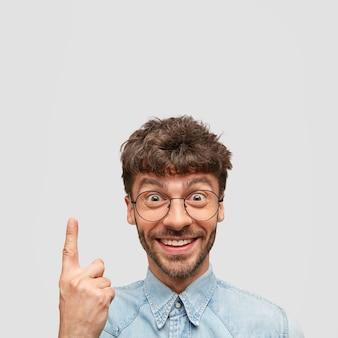 Ainda bem que engraçado homem designer com expressão positiva, indica para cima, satisfeito por terminar o trabalho, apresenta resultados, tem sorriso encantador