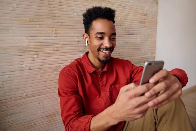 Ainda bem que jovem bonito, cabelo curto, pele escura, cara encaracolado segurando um telefone celular e sorrindo alegremente enquanto lê as mensagens, posando no interior bege com uma camisa vermelha