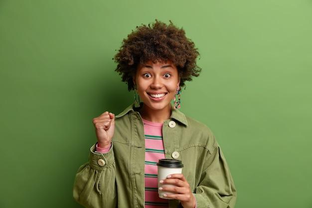 Ainda bem que jovem cerrou os punhos celebrando notícias positivas, sorrindo alegremente, bebendo café para viagem e usando roupas elegantes isoladas sobre a parede verde