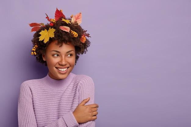 Ainda bem que mulher de cabelo encaracolado se vira de lado, tem olhar alegre, estando satisfeita com algo incrível, usa roupa casual, folhas de bordo na cabeça, sorri agradavelmente, posa dentro de casa
