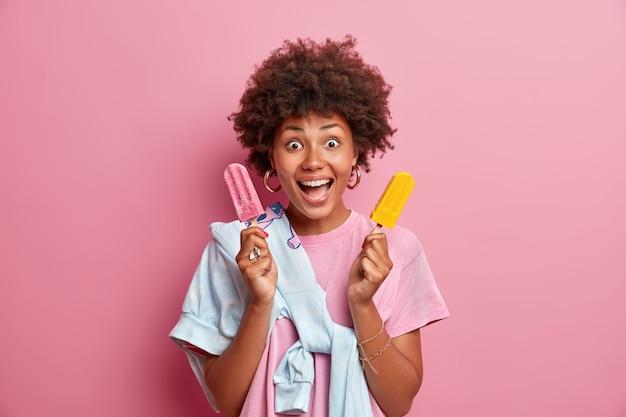 Ainda bem que mulher de pele escura segura dois sorvetes gelados, mantém a boca aberta, se trata com uma sobremesa deliciosa, desfruta de um sabor agradável, poses