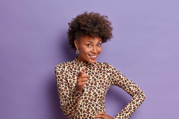 Ainda bem que mulher estilosa aponta o dedo indicador para você, olha com expressão feliz, escolhe alguém, sugere algo bom, vestida de gola alta, estampa de leopardo