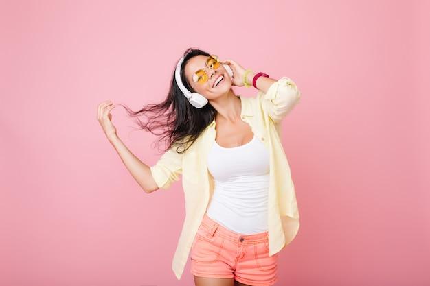 Ainda bem que mulher latina com cabelo preto balançando, dançando e sonhando com algo. mulher alegre em acessórios coloridos curtindo música e sorrindo