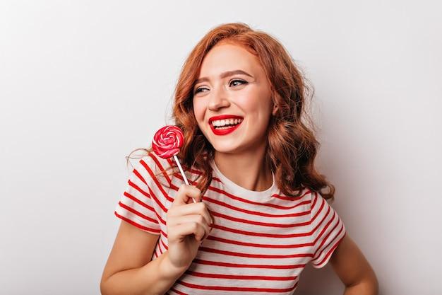 Ainda bem que mulher ruiva segurando pirulito e rindo. glamourosa garota caucasiana com doces, aproveitando a sessão de fotos.