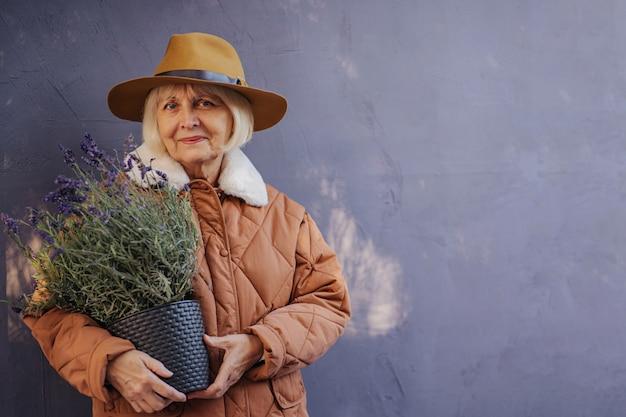 Ainda bem que mulher sênior em agasalhos elegantes e chapéu, sorrindo para a câmera e carregando vasos de lavanda