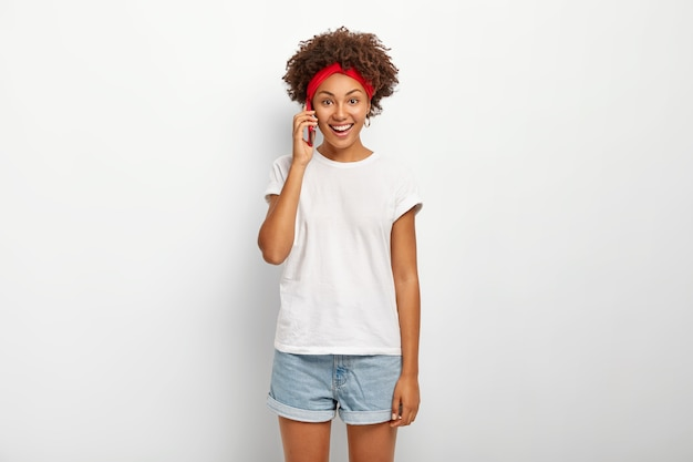 Ainda bem que mulher sorridente segura o smartphone perto da orelha, fala casualmente com um amigo, tem um sorriso largo, mostra os dentes