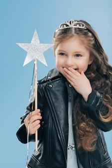 Ainda bem que o garoto pequeno e agradável cobre a boca com a palma da mão, ri positivamente, usa coroa e jaqueta de couro preta