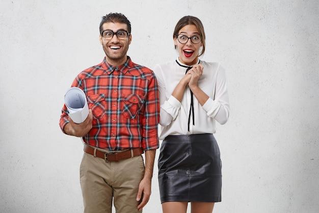 Ainda bem que os trabalhadores criativos masculinos e femininos se sentem entusiasmados: um homem engraçado e desajeitado com desenhos e uma bela mulher com roupas formais