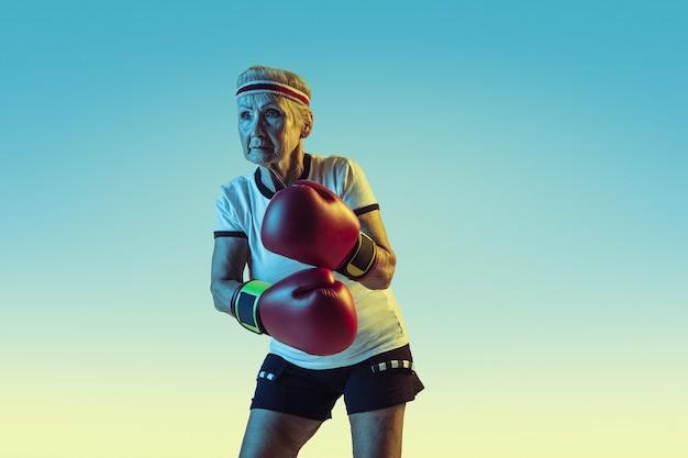 Ainda chutando. mulher sênior em roupas esportivas boxe em gradiente