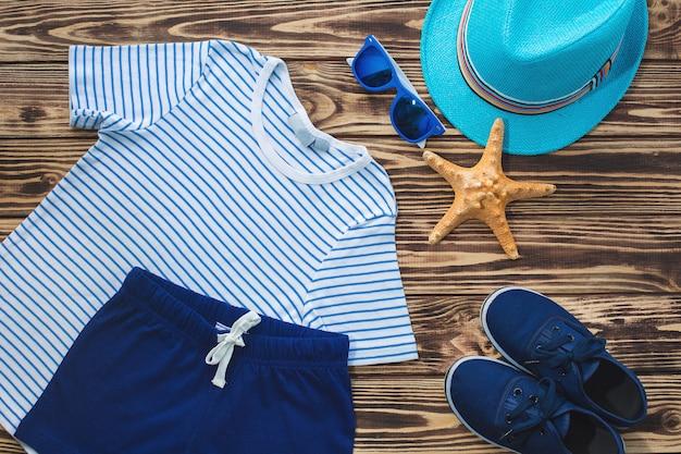 Ainda plana de desgaste infantil. guarda-roupa infantil. roupas de praia e férias para um menino. fundo de madeira