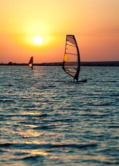 Ainda superfície do mar, homem praticando windsurf e pôr do sol dourado no céu
