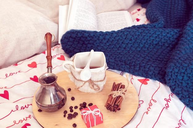 Ainda vida aconchegante do café da manhã na cama para o dia de são valentim. café com presentinho e manta com livro sobre fundo em período de isolamento