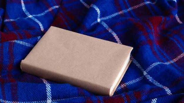 Ainda vida aconchegante. um livro fechado com um cobertor xadrez de lã azul e vermelho quente. espaço de cópia grátis. layout de inverno e outono com capa de livro em branco. fundo quente e festivo.