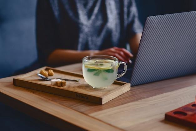 Ainda vida aconchegante xícara de chá, biscoitos no fundo de uma garota atrás de um laptop