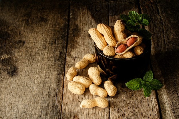 Ainda vida casca de amendoim aberta para mostrar a semente no lado na madeira