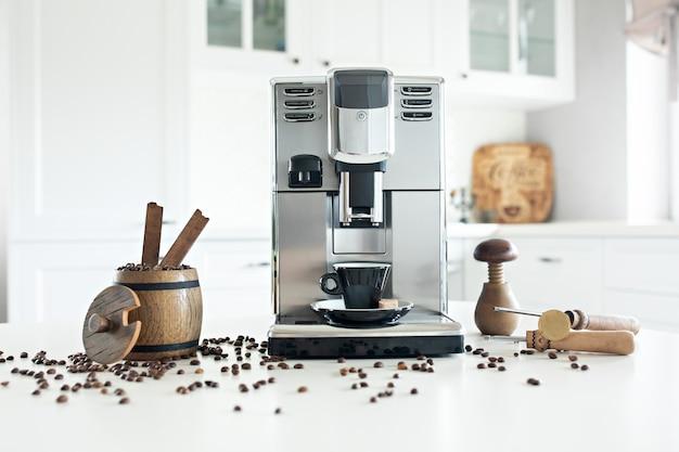 Ainda vida com a máquina de café caseiro na mesa de cozinha com o recipiente de madeira com feijões de café.