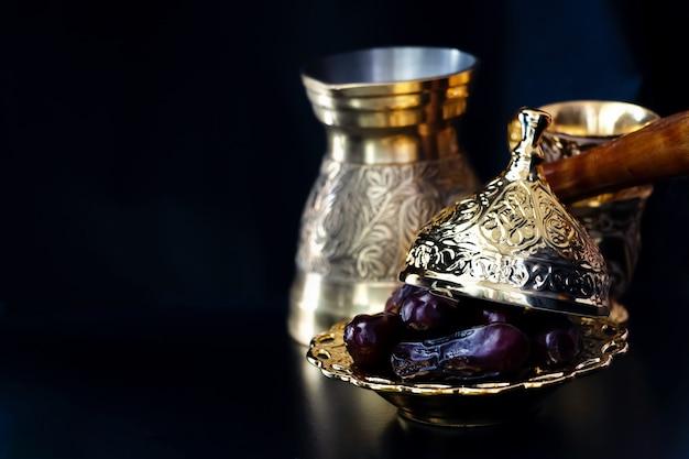 Ainda vida com grupo de café árabe dourado luxuoso tradicional com jezva, copo e datas. conceito de ramadã.