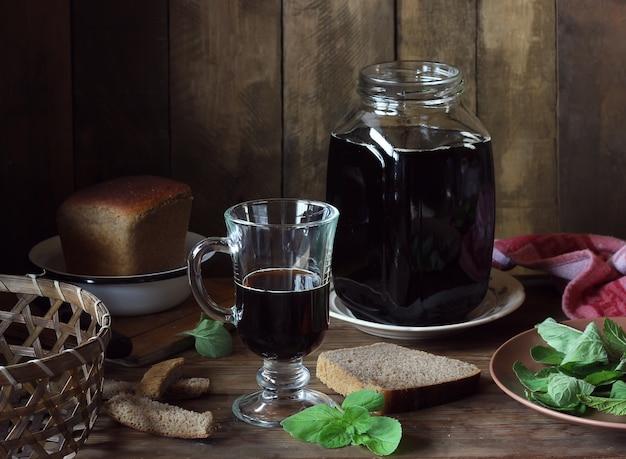 Ainda vida com kvass em um frasco de vidro, pedaços de pão de centeio e folhas de hortelã.