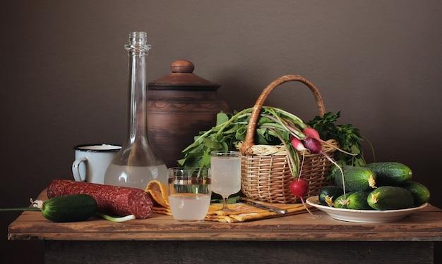 Ainda vida com moonshine, legumes frescos na cesta e salsicha em um estilo rústico.