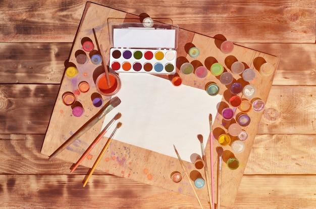 Ainda vida com papel em branco, pincéis e frascos de tinta aquarela e guache