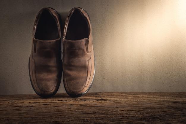 Ainda vida com sapatos masculinos na mesa de madeira contra a parede do grunge