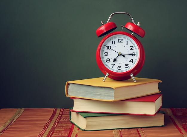 Ainda vida com três livros em cores e um despertador vermelho