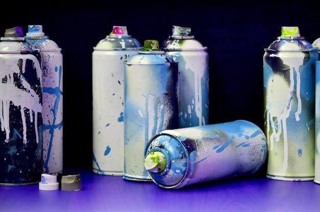 Ainda vida com um grande número de latas de pulverizador coloridas usadas do aerossol