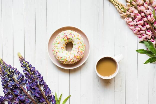 Ainda vida com uma filhós da xícara de café e das flores do lupine em uma tabela de madeira clara.