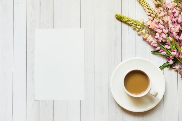 Ainda vida com uma xícara de café e um tremoço floresce o bloco de notas sobre uma mesa de madeira de luz. espaço da cópia