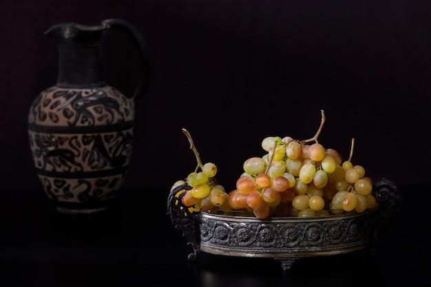 Ainda vida com uvas brancas e jarro antigo no fundo preto.