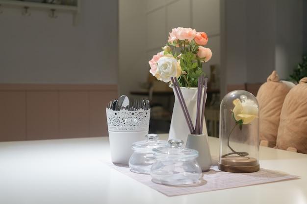Ainda vida da sala de jantar. feche acima da mesa de jantar decorada com as flores cor-de-rosa no vidro e no vaso pequenos com a cozinha no fundo.