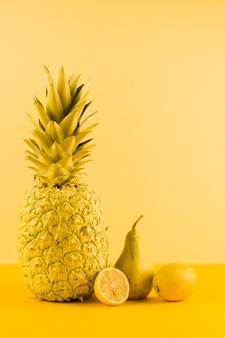 Ainda vida de abacaxi; limão e peras contra pano de fundo amarelo