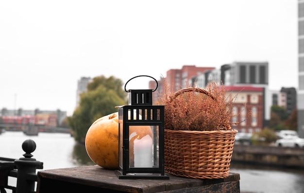Ainda vida de abóbora, lâmpada, cesta de vime, aterro da cidade, decoração, rua, halloween.