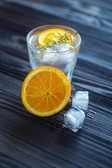 Ainda vida de bebida refrescante com cubos de gelo e fatia de laranja