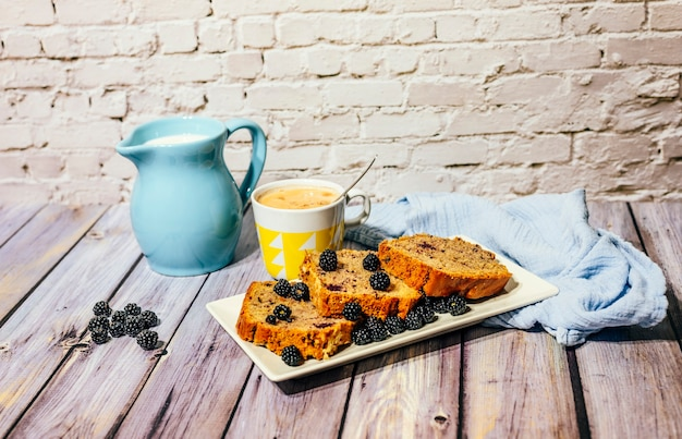 Ainda vida de bolo de frutas silvestres com copo de leite com cacau e jarro de leite.