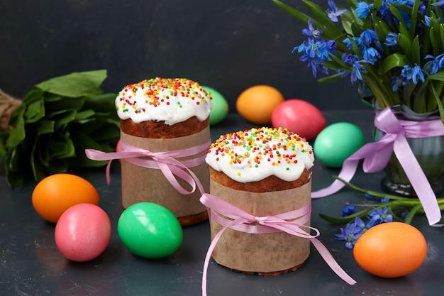 Ainda vida de bolos de páscoa, ovos pintados e flocos de neve da floresta em fundo escuro