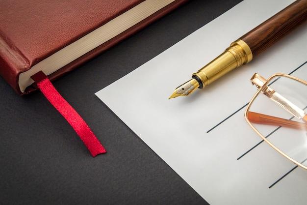 Ainda vida de escritório em mesa preta com caneta na folha e bloco de notas