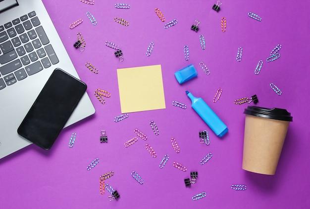 Ainda vida de escritório minimalista. laptop, artigos de papelaria, xícara de café, smartphone em fundo roxo.