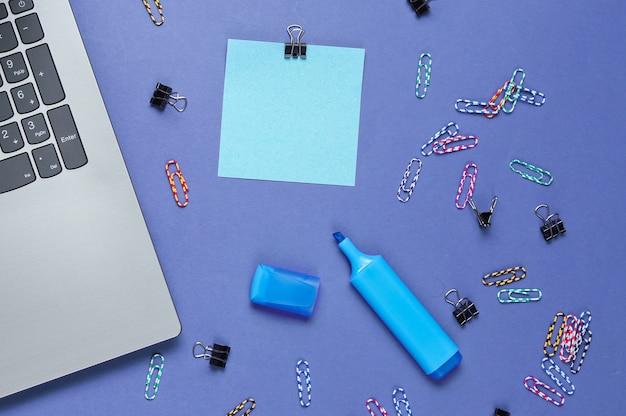 Ainda vida de escritório minimalista. laptop, papelaria em roxo