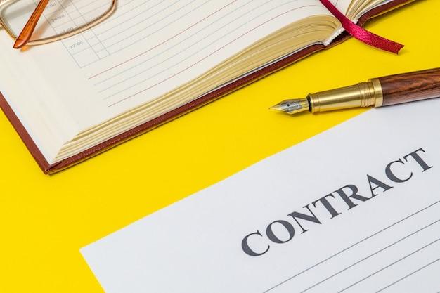 Ainda vida de escritório na mesa amarela com uma caneta dourada, caderno e preparação de contrato para anotações