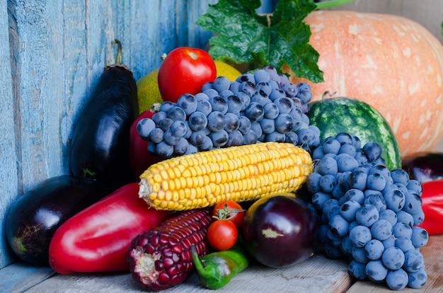 Ainda vida de milho, uvas, berinjela, abóboras e pimentos no fundo antigo.