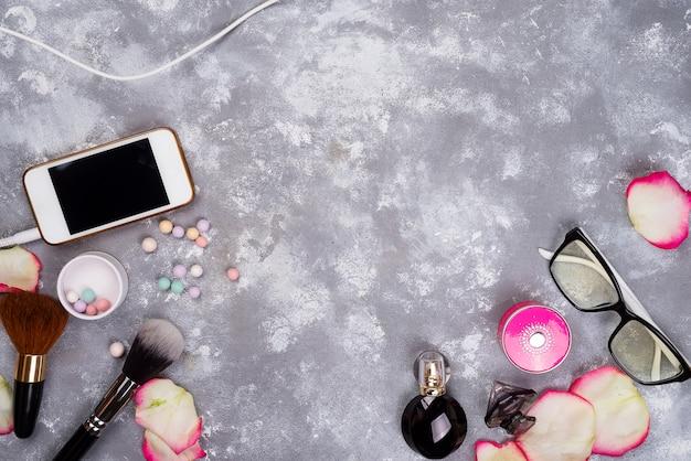 Ainda vida de moda mulher. moda feminina com pétalas de rosas, cosméticos, telefone