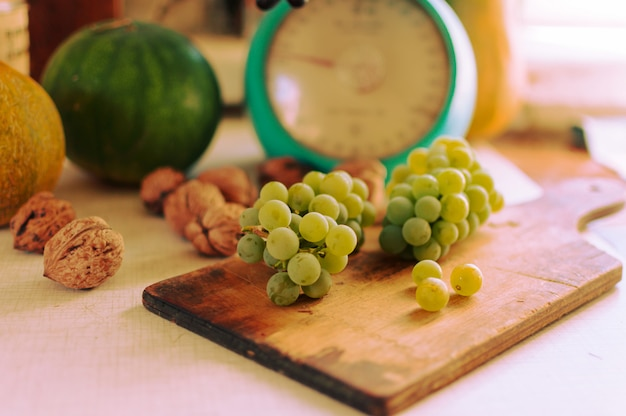 Ainda vida de outono. uvas verdes mentem na placa de madeira. são abóboras, nozes e escamas. colheita de outono