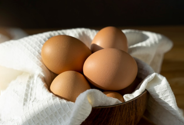 Ainda vida de ovos de galinha em uma tigela na mesa de madeira na cozinha. ovos ao ar livre, produtos naturais da fazenda. comida saudável durante