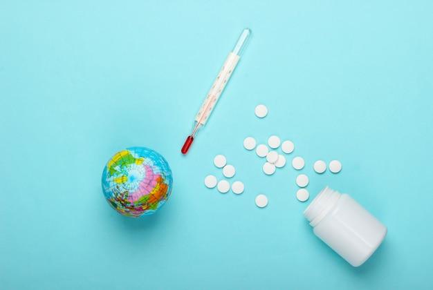 Ainda vida de pandemia global. globo, termômetro com frasco de comprimidos sobre fundo azul. surto de coronovírus