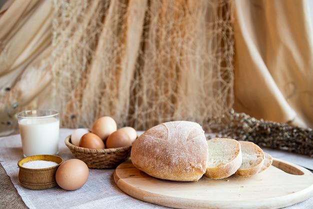 Ainda vida de pão, leite, ovos e sal em placas de madeira