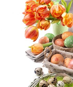 Ainda vida de páscoa com tulipas laranja e decorações de páscoa