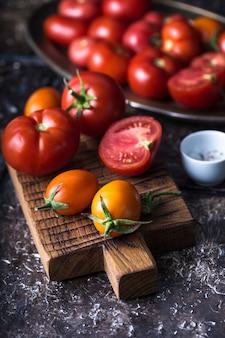 Ainda vida de tomates maduros na placa de madeira, mesa marrom, fatia de tomate