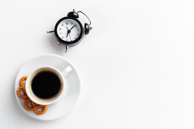 Ainda vida, despertador vintage e xícara de café na mesa branca